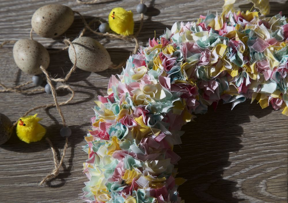 Simple spring fabric wreath on a grey wood background with decorative eggs and little yellow pom pom chicks.
