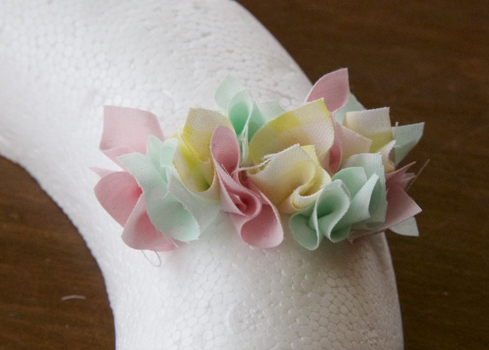 Making a simple spring wreath, fabric scraps in pastel colours pushed into a polystyrene wreath base