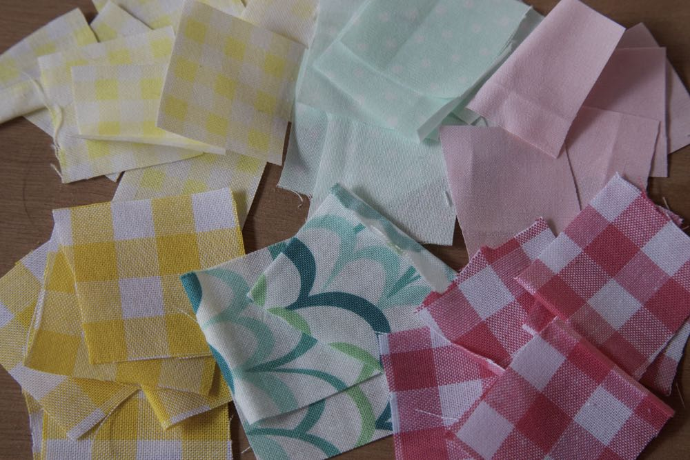 Fabric scraps in spring colours laid out on a table to make a spring wreath