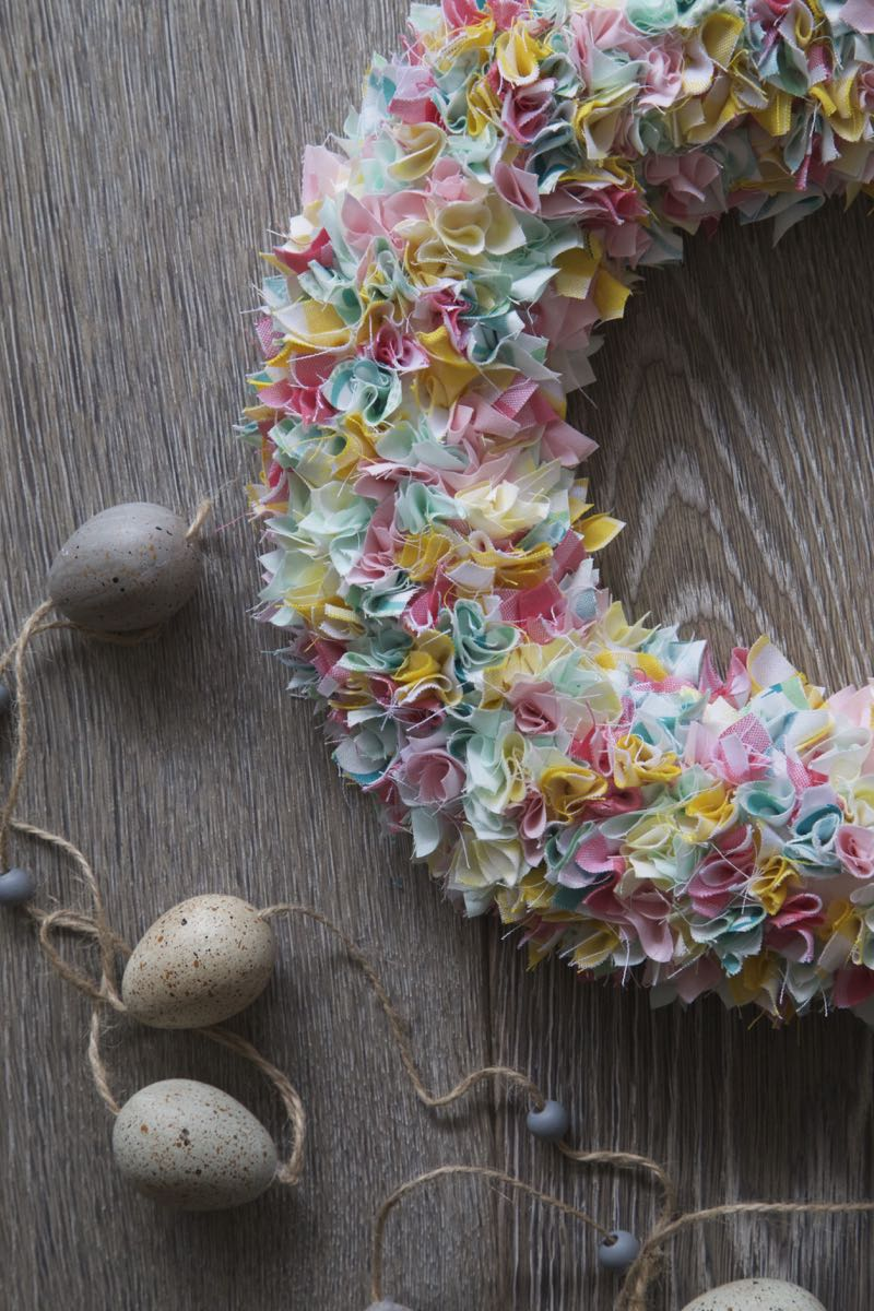 Simple Spring Wreath on a grey wooden board with a string of grey eggs.