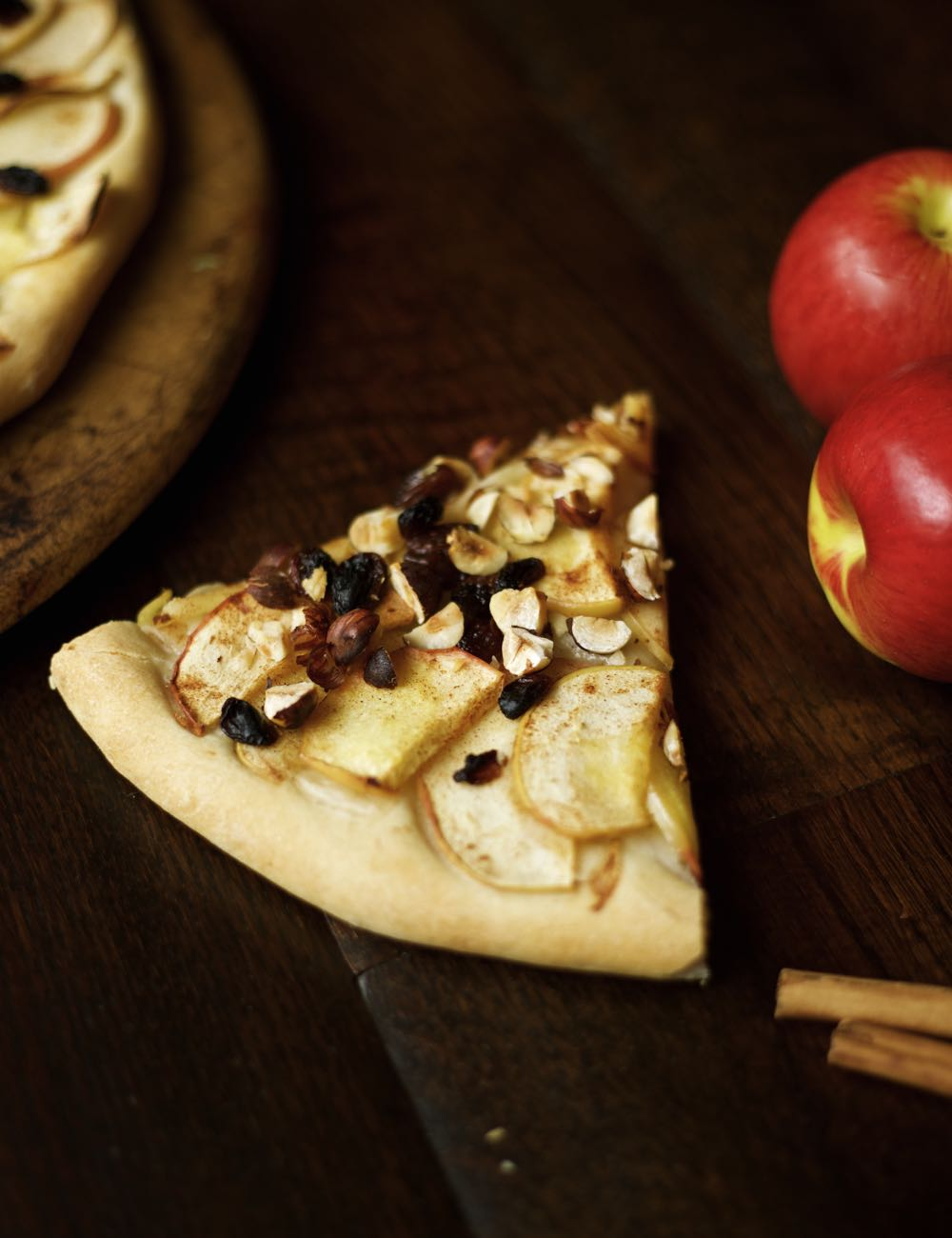 A slice of apple and hazelnut pizza with juicy red apples and cinnamon.