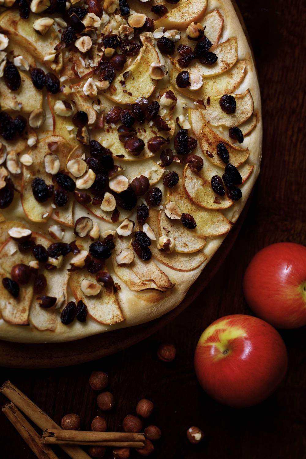 Dessert pizza topped with apples hazelnuts and sultanas.