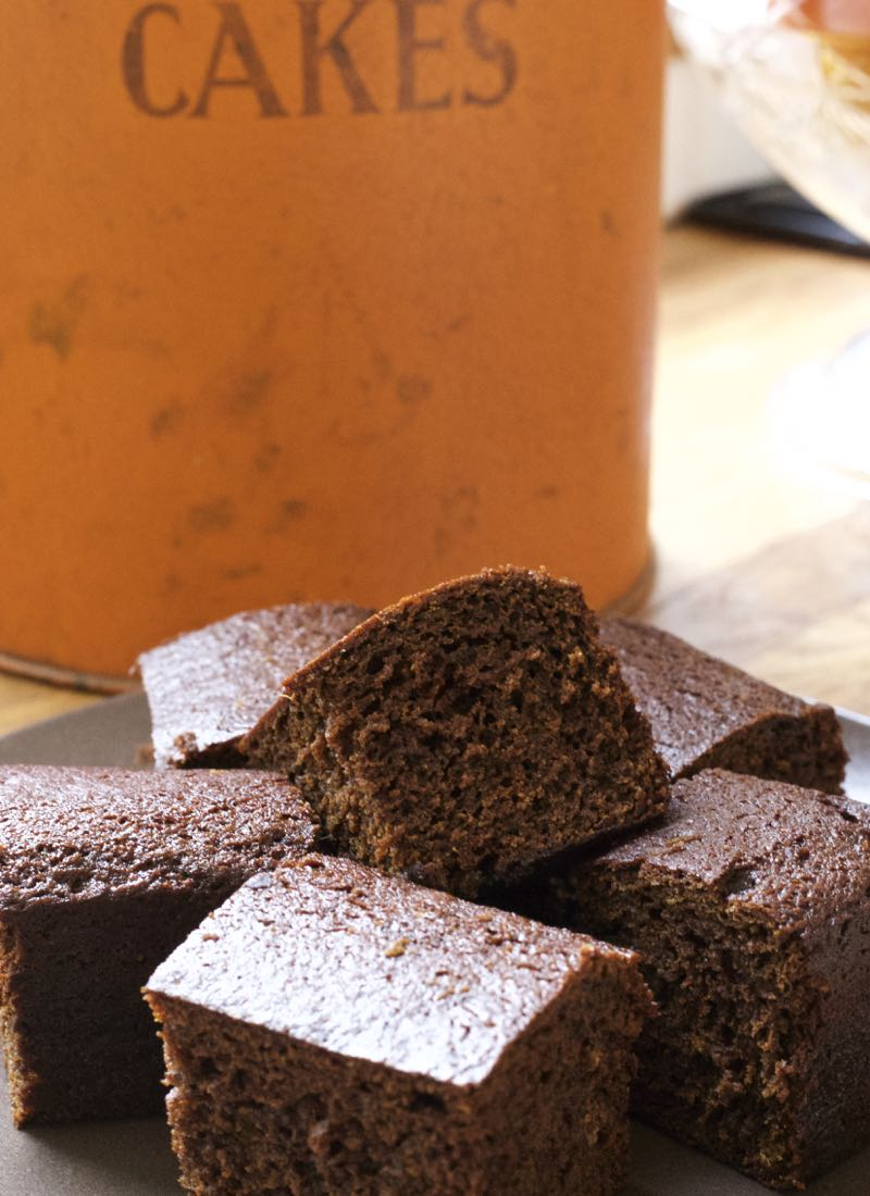 Squares of sticky ginger cake with an orange vintage cake tin in the background.