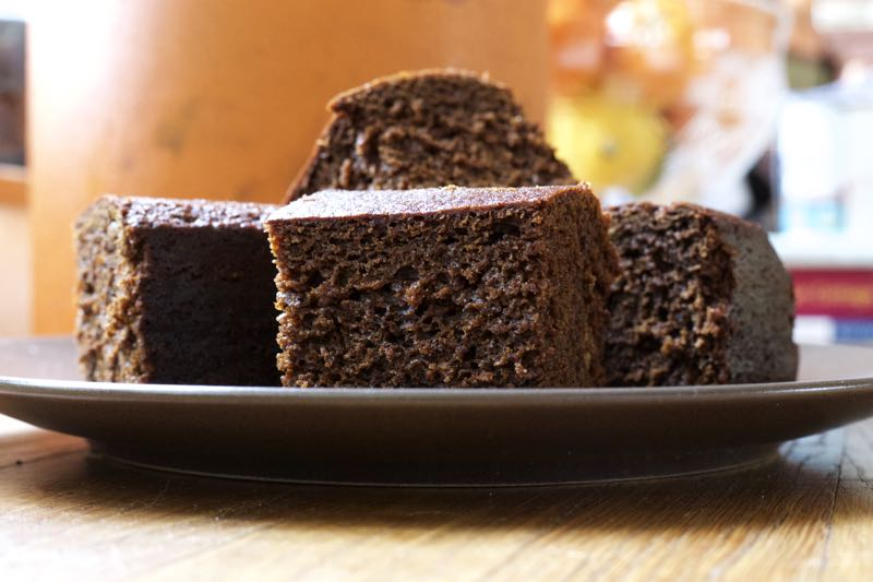 Thick slices of sticky ginger cake on a brown plate.