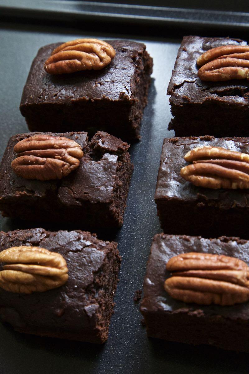 Easy traybake brownies, vegan pumpkin brownies topped with pecan nuts.