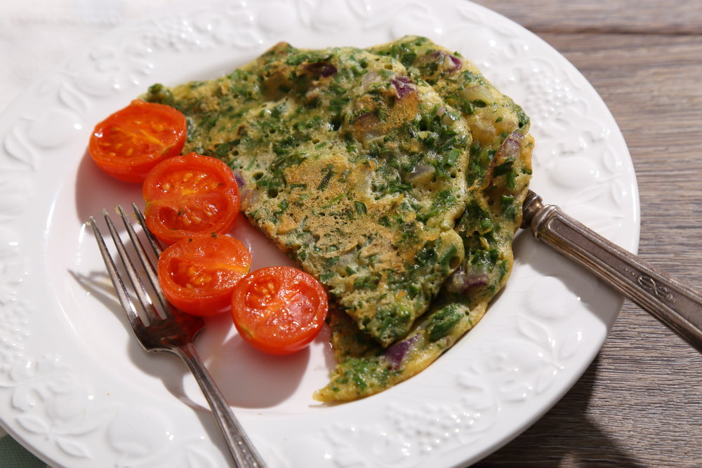 Fresh Herb Vegan Omelette served with gently fried tomatoes.