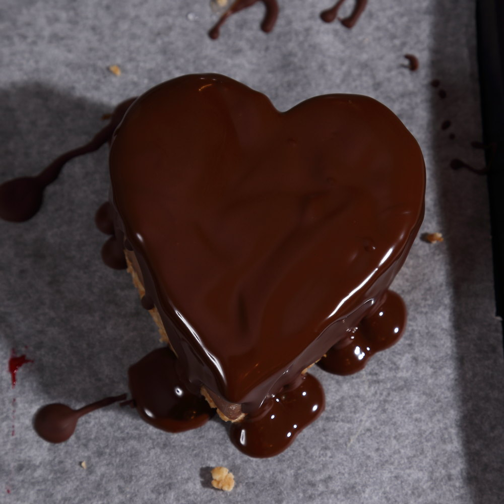 Vegan chocolate heart tart, topped with melted chocolate.
