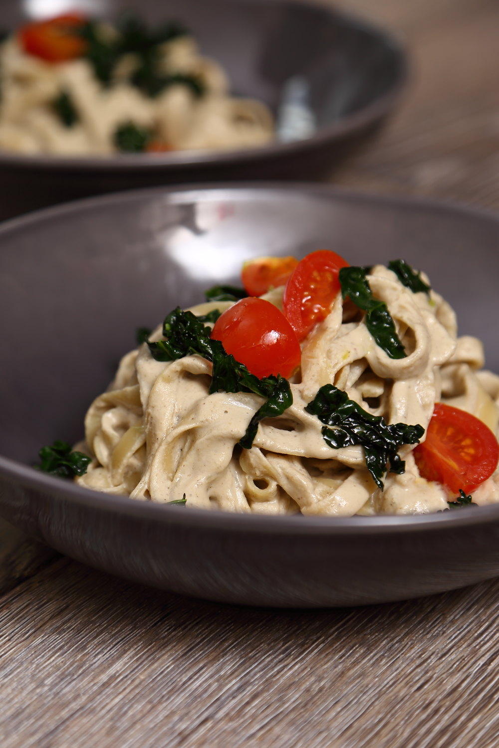 Vegan Alfredo Sauce - Vegan Pasta Alfredo served with black kale and cherry tomatoes.