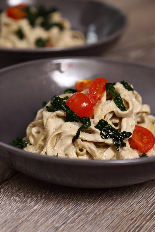 Vegan Alfredo Sauce - Vegan Pasta Alfredo served with black kale and cherry tomatoes.