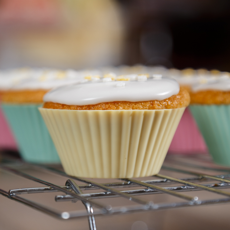 Side view of Vegan lemon cupcakes topped with glace icing standing on a cooling rack.