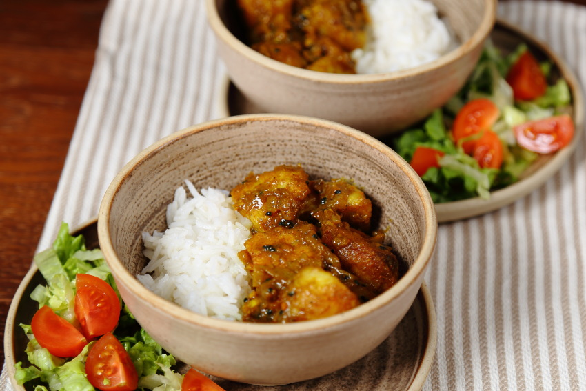 Roast Potato Curry in rustic bowls with rice and salad.