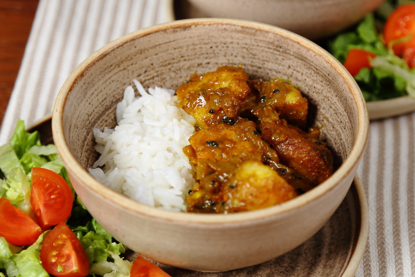 Roast Potato Curry Served with Basmati Rice in a rustic bowl.
