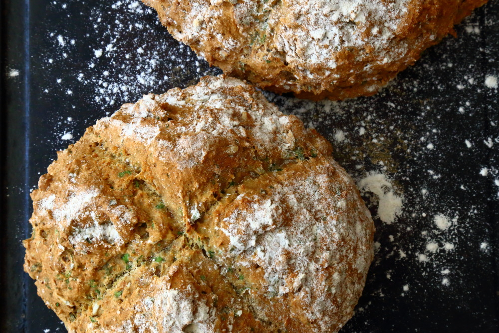Vegan Soda Bread with herbs, dusted with flour.