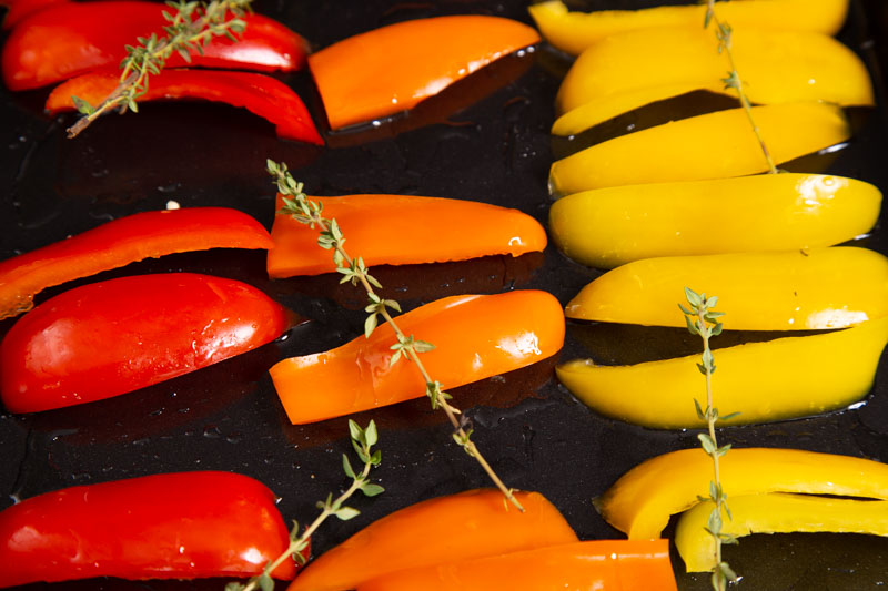 Red, orange and yellow peppers ready for roasting with thyme.