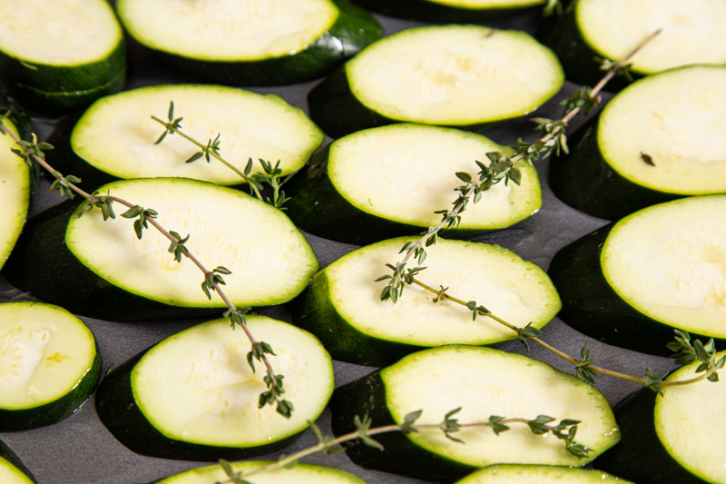 Courgettes, sliced on the diagonal to roast with olive oil and thyme.