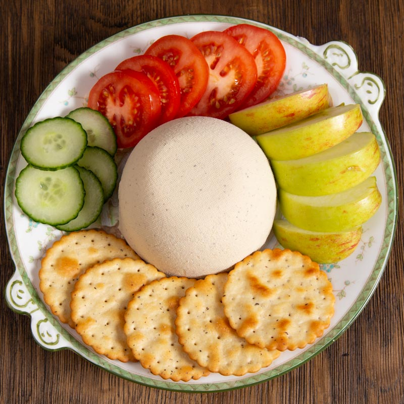 Homemade Cashew Cheese with crackers and slices of apple, tomato and cucumber.