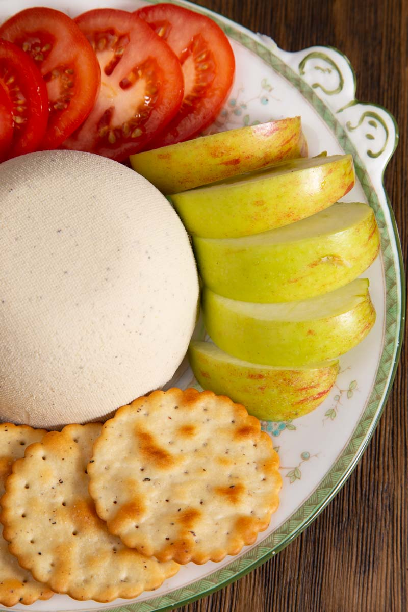 Homemade Nut Cheese surrounded by crackers, apple and tomato.