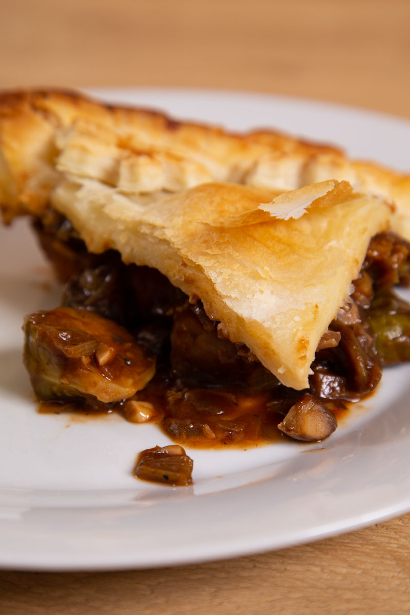 Vegan Mushroom Pie, topped with puff pastry and served on a white plate.