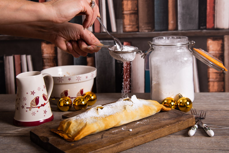 Sprinkling icing sugar on a Christmas strudel