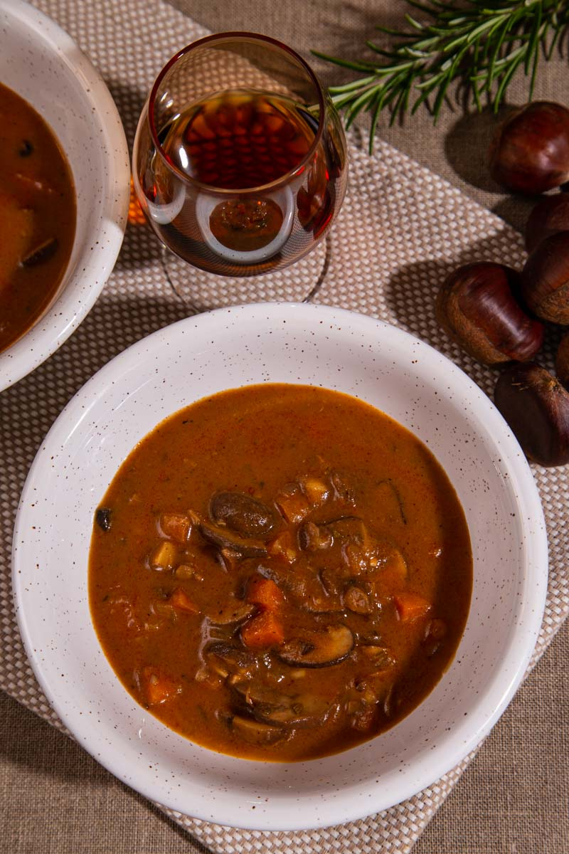 A bowl of chestnut and mushroom soup with a glass of sherry.