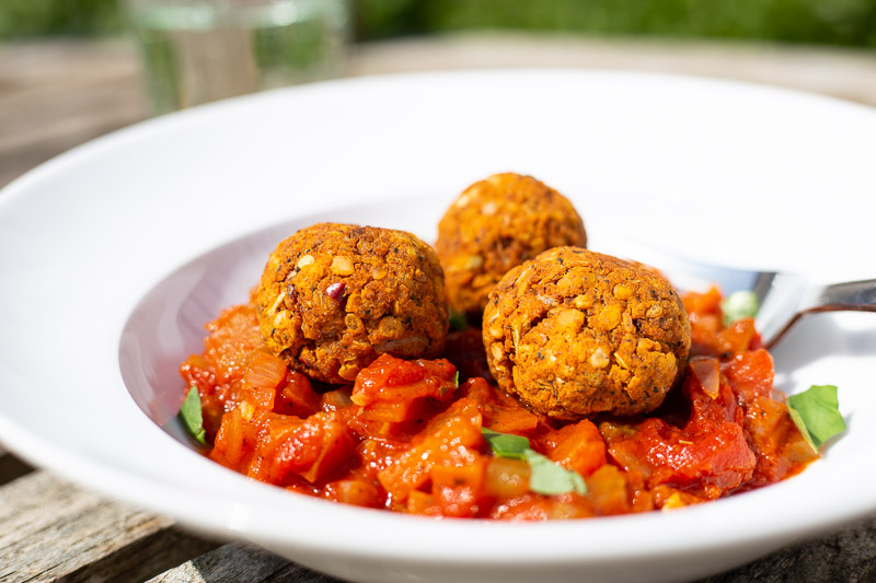 A dish of vegan meatballs with tomato and vegetable sauce.