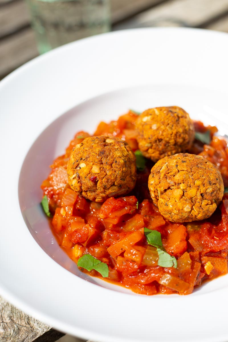 A bowl of vegan lentil meatballs with fresh tomato sauce.