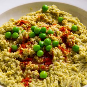 A bowl of split pea hummus topped with fresh green peas and paprika