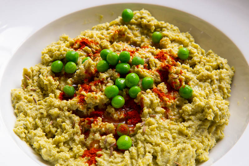 A bowl of split pea hummus topped with fresh green peas and paprika.