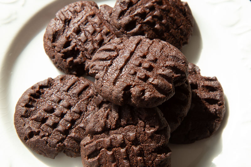 Chocolate biscuits on a white plate in the sunshine.