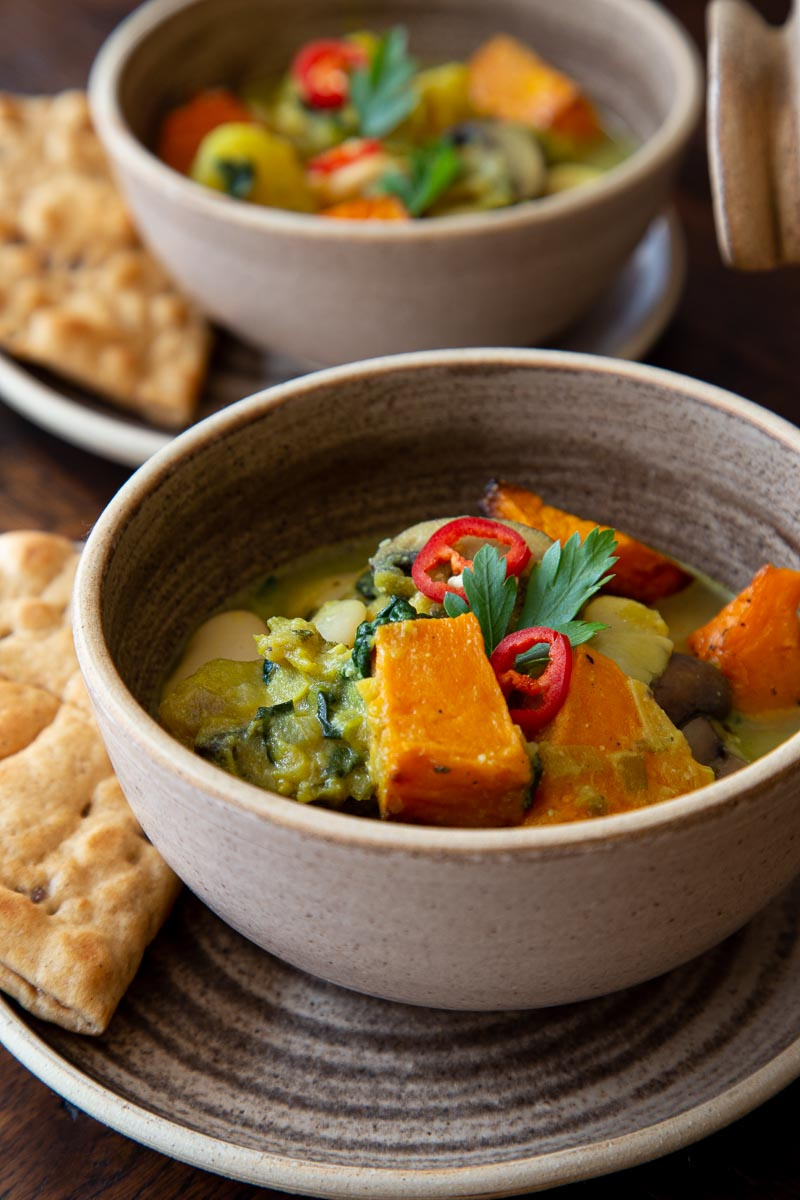 Pumpkin Stew with Butterbeans and Mushrooms, topped with chilli, served in rustic bowls.