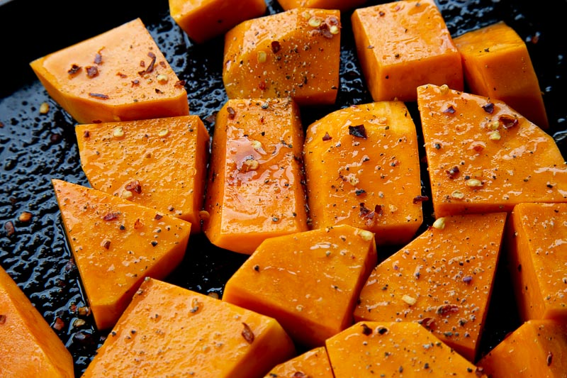 Chunks of butternut squash ready to roast on a baking tray.