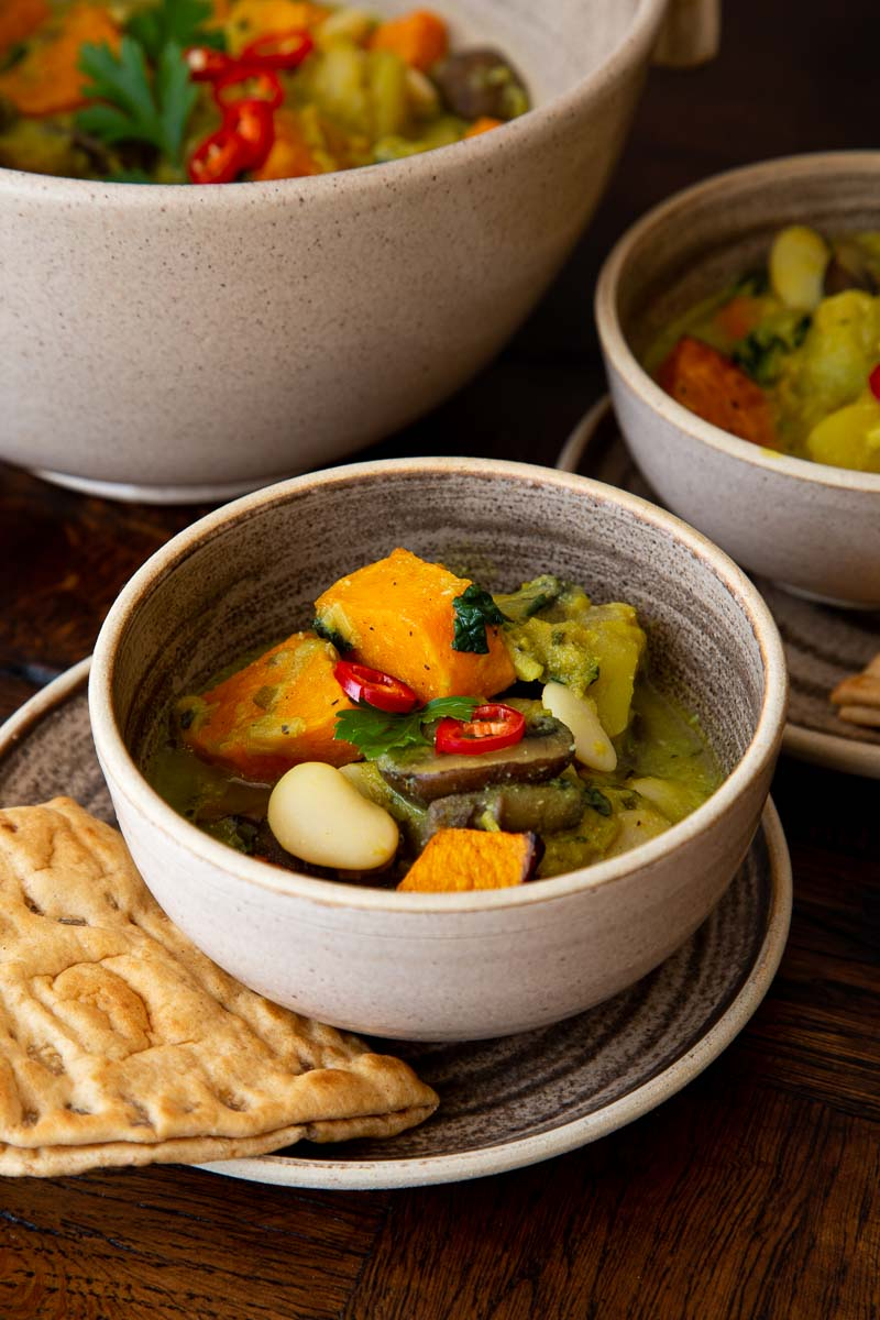 Pumpkin and Butterbean Stew in rustic bowls with flatbreads on the side.