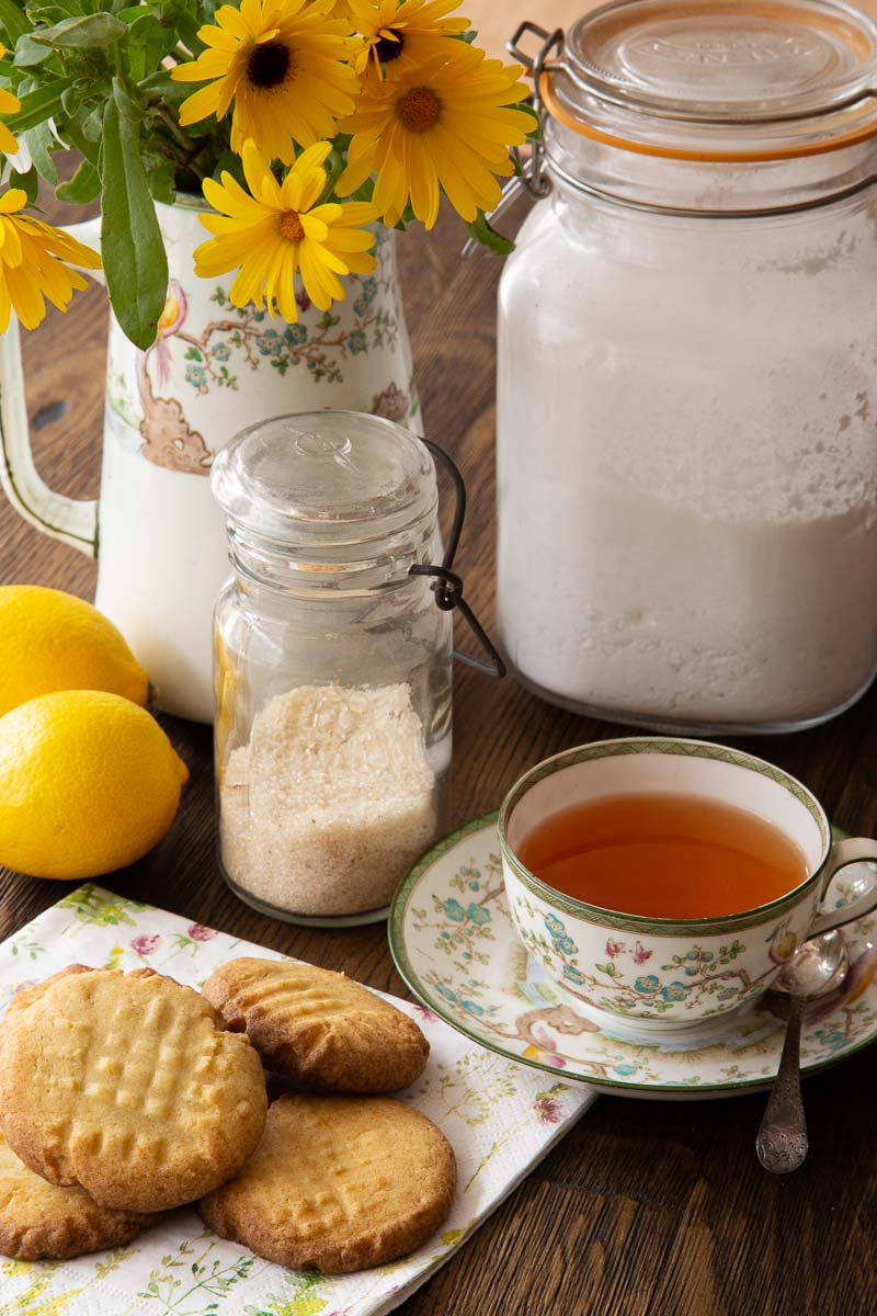 A vase of summer flowers, a cup of redbush tea, lemon fork biscuits and the ingredients to make them.