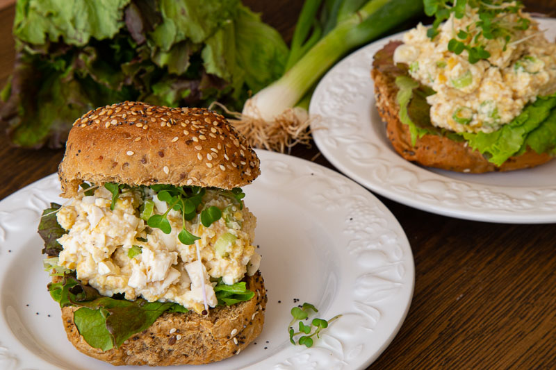 vegan chickpea mayo served in a brown roll with salad and cress.