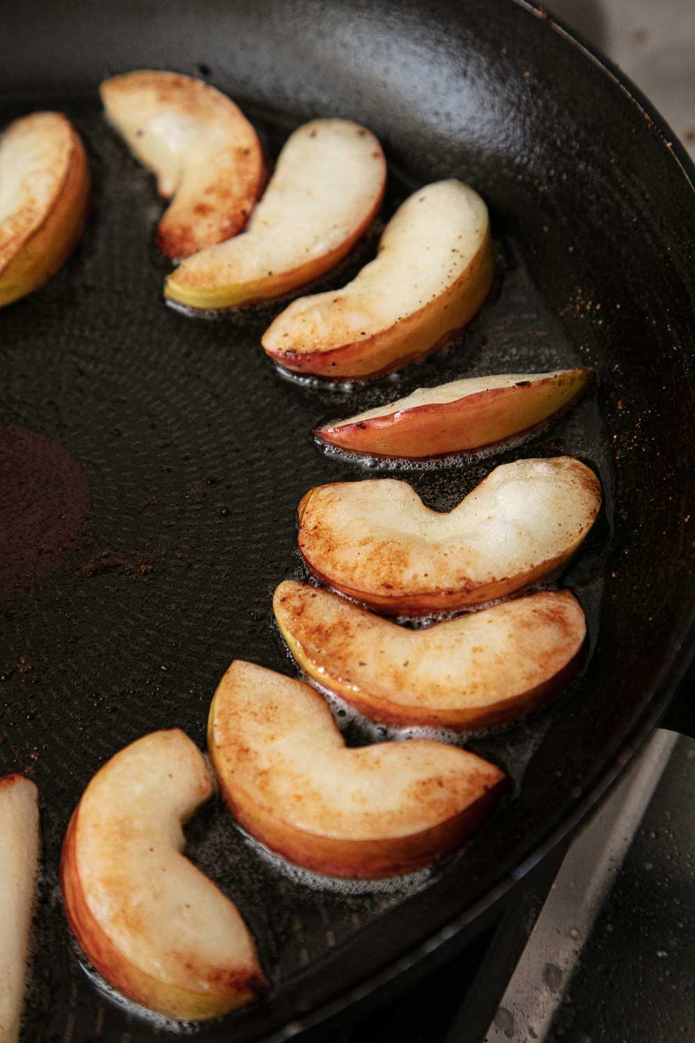 Apple slices frying in a frying pan.