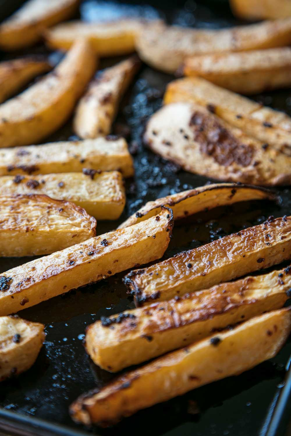 Roasted swede chips on a baking tray.