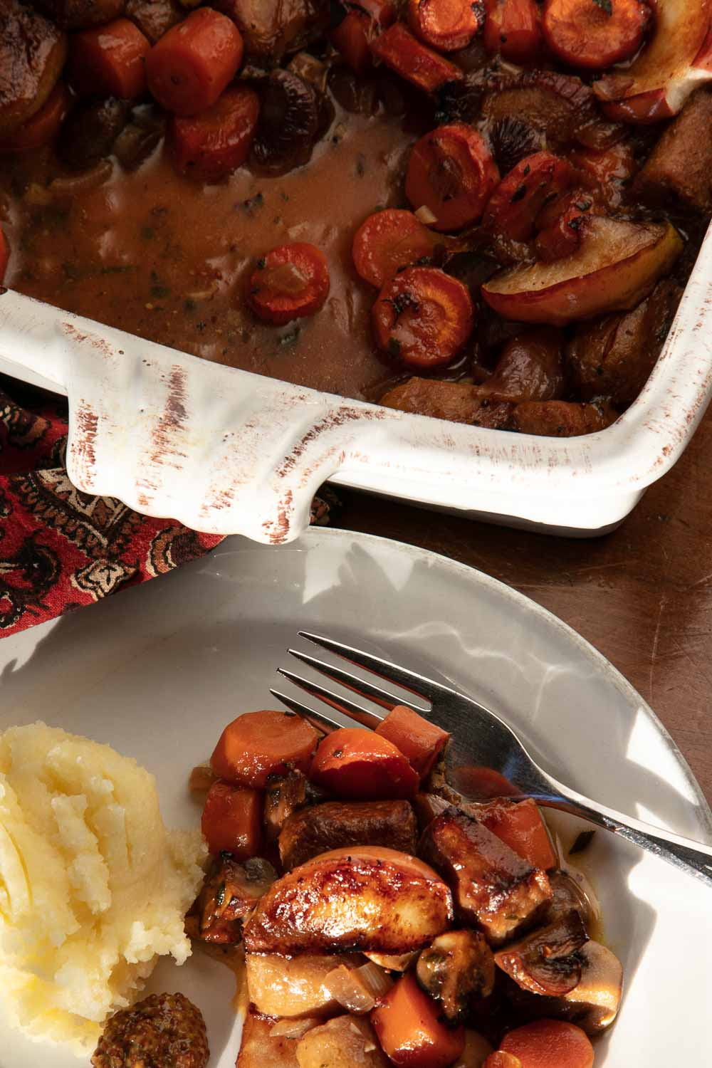 Vegan Sausage Casserole in a casserole dish and a serving on a plate with mashed potatoes.