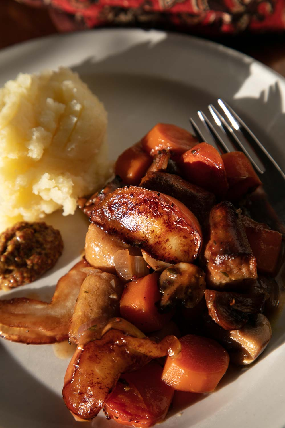 Vegan Sausage and Apple Casserole served with mashed potato and grain mustard.