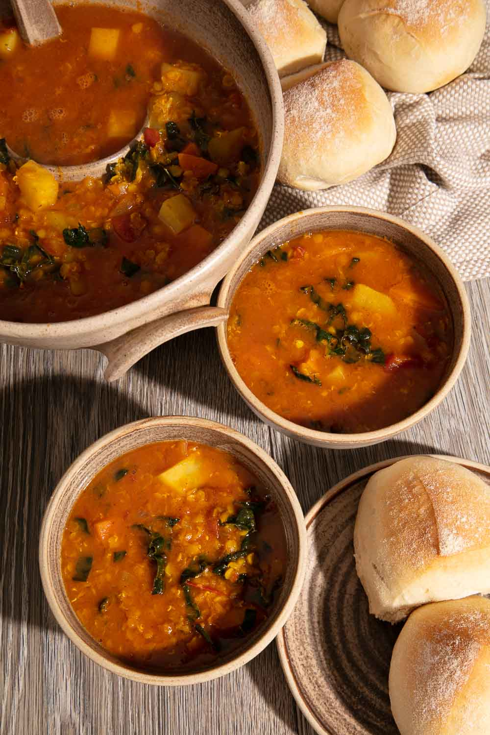 Two bowls and a tureen of Lentil and Winter Vegetable Soup with soft bread rolls.