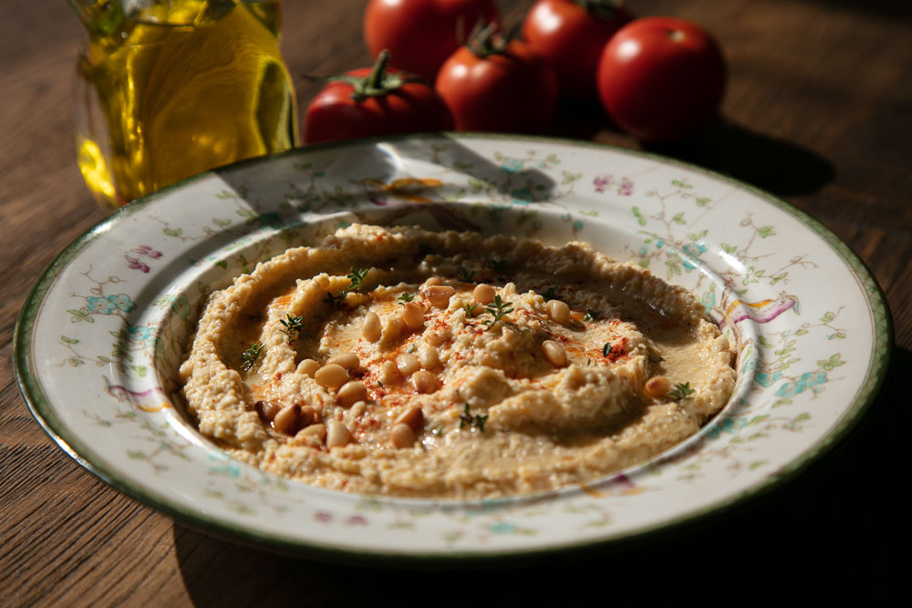 A bowl of hummus topped with pine nuts, paprika and thyme.