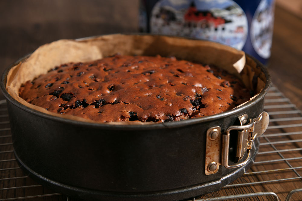 A large vegan fruit cake in a cake tin.