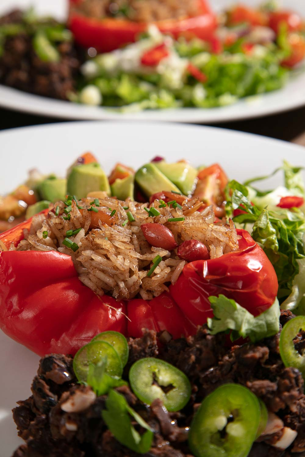 A plump red pepper stuffed with spiced rice. Served with refried black beans and avocado salsa.