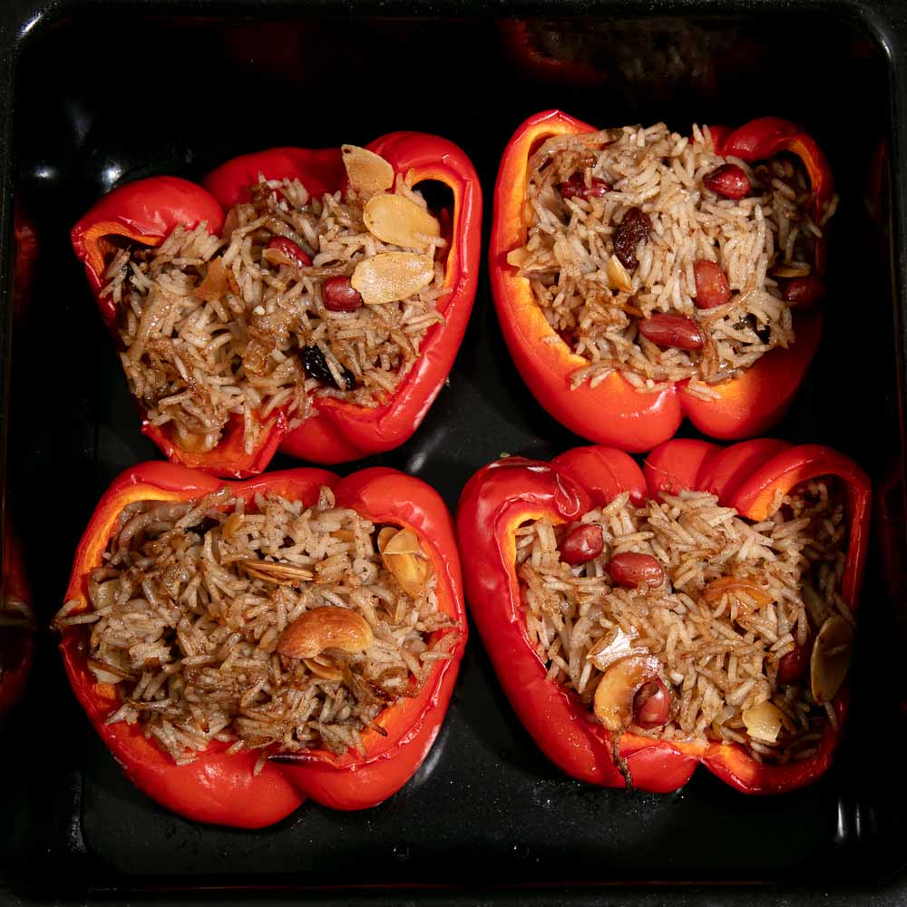 Stuffed peppers with spiced rice in a black roasting tin.