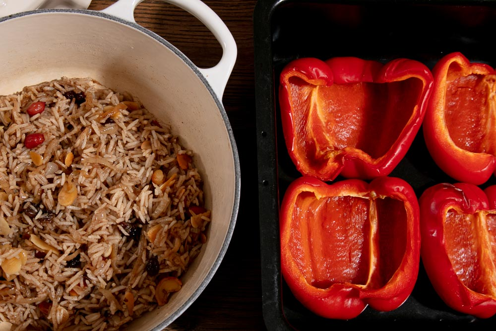 A pan of spiced rice and a tin of roasted red pepper halves.