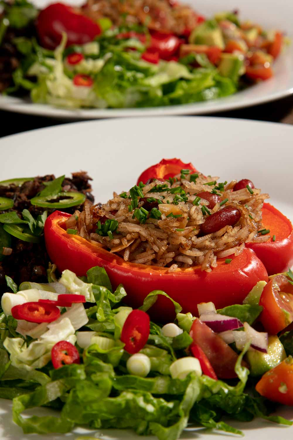 Vegan Stuffed Peppers filled with spiced rice and served with salad.