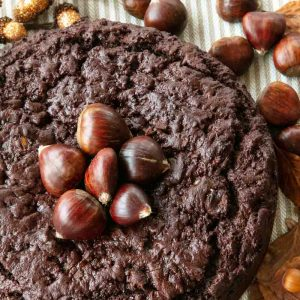 Chestnut and Chocolate Cake topped with Fresh Chestnuts, surrounded by autumnal decorations.