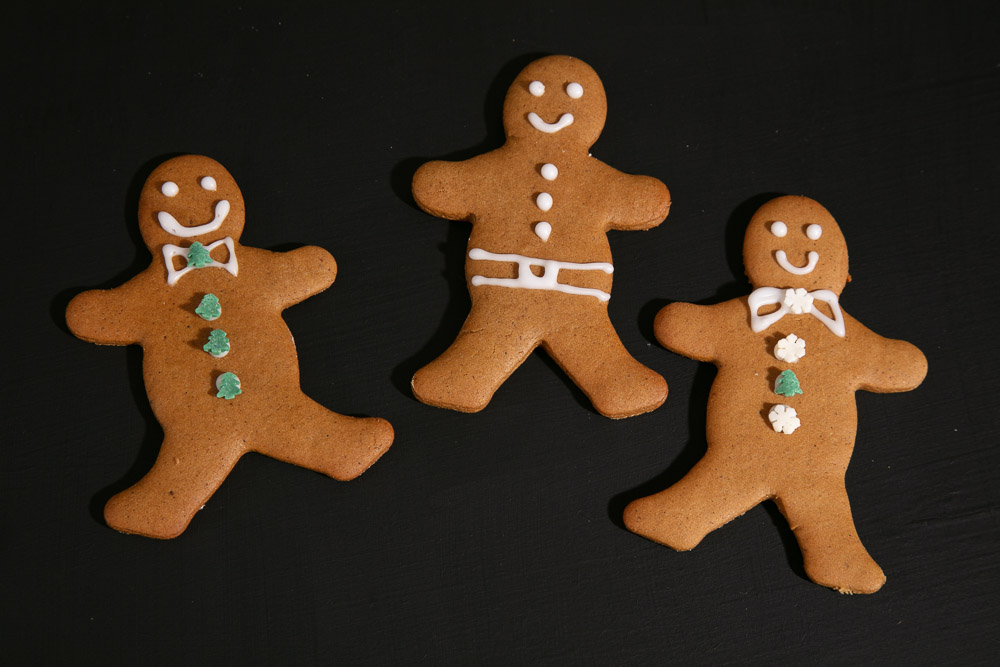 Three vegan gingerbread men decorated with glace icing clothes.