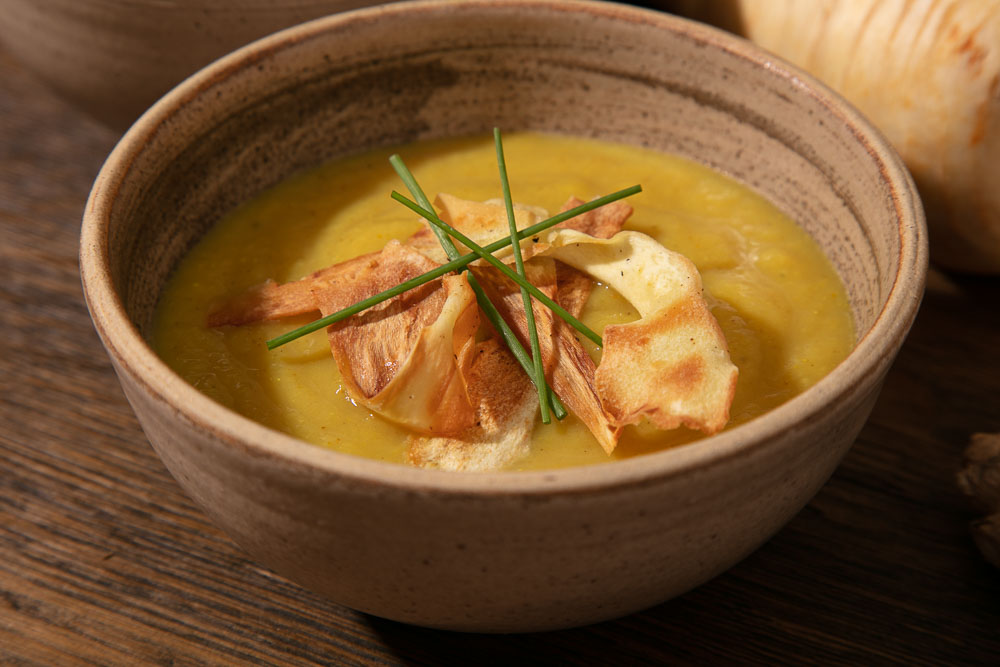 Parsnip Soup topped with Parsnip Crisps and Chives.
