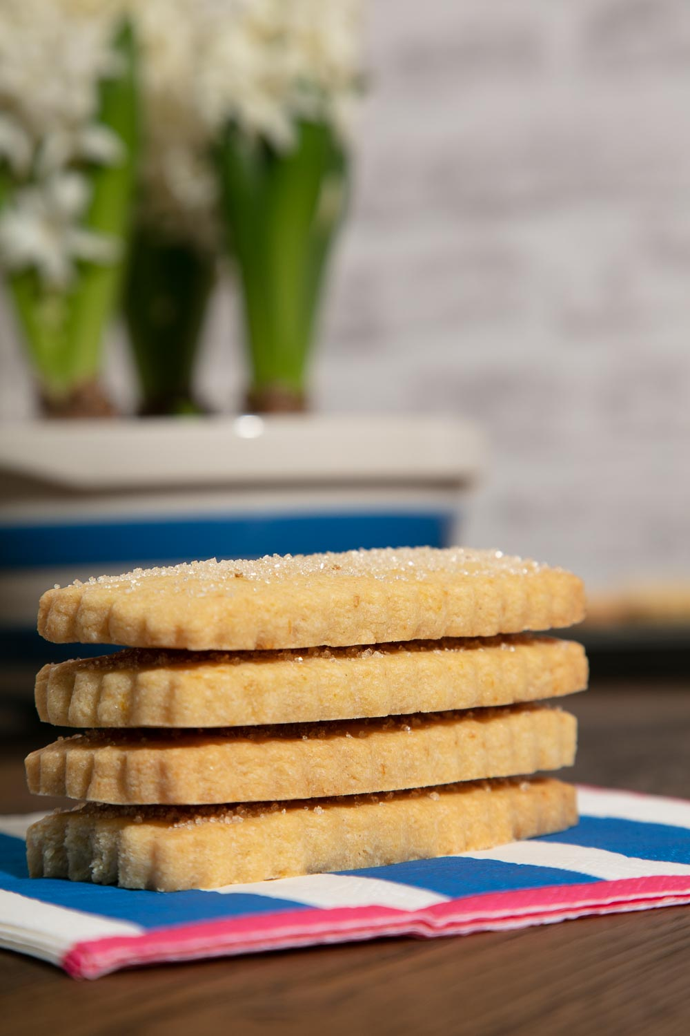 A stack of shortbread biscuits on a striped napkin.