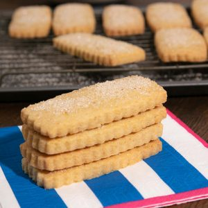 A stack of vegan shortbread biscuits on a blue and white striped napkin.